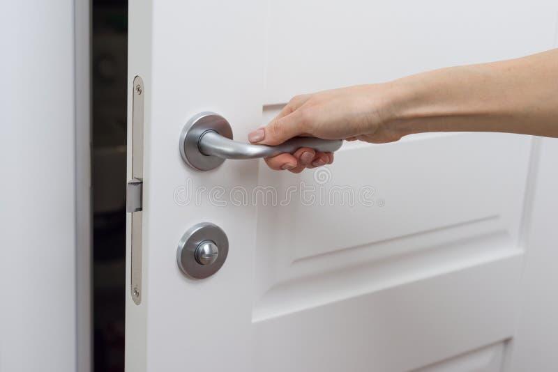 Handen öppnar dörren litet Detaljen av en vit inredörr med ett kromdörrhandtag och låser arkivfoto