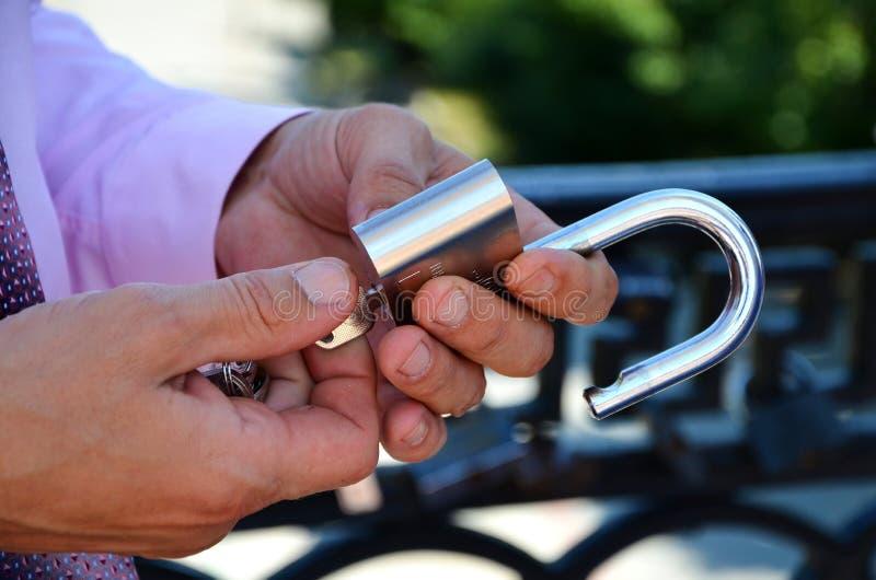 Handen öppnar ett key lås royaltyfri foto