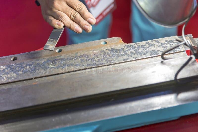 Handen av arbetare som skrapar glidbanavägen fotografering för bildbyråer