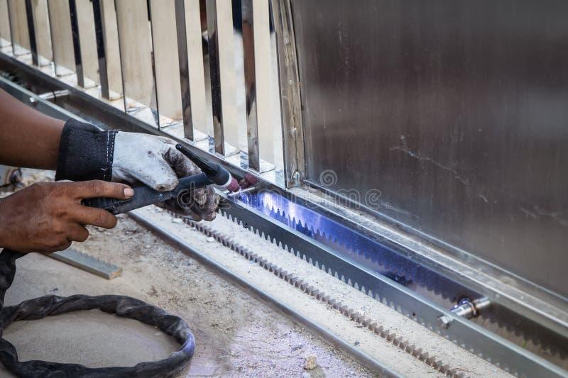 Handen av arbetarmannen som svetsar en rostfritt ståldörrram överträffar in royaltyfria foton