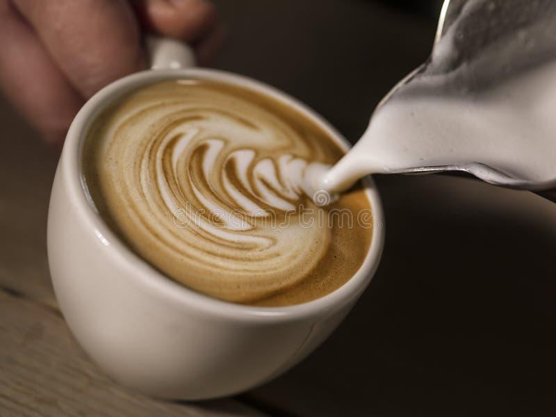 Handen av att hälla för kaffe för baristadanandecappuccino mjölkar danandelaten arkivfoto
