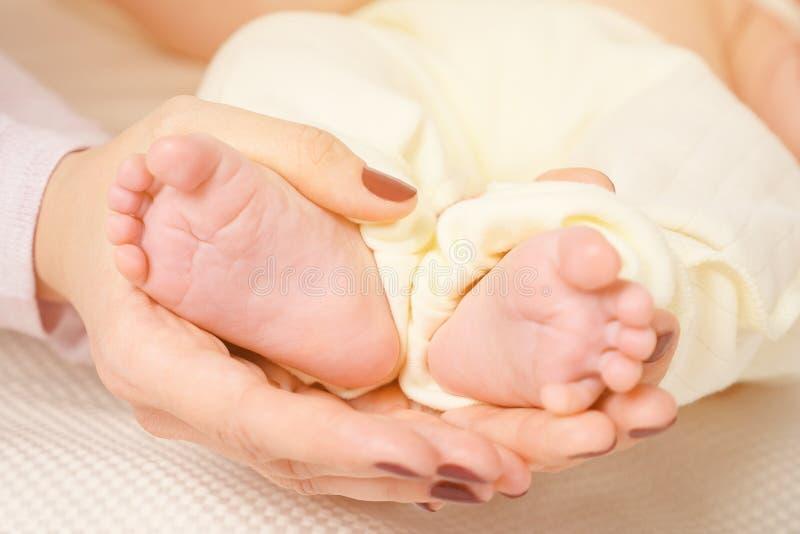 Handen av att sova behandla som ett barn i handen av moderslutet upp på sängen arkivbild