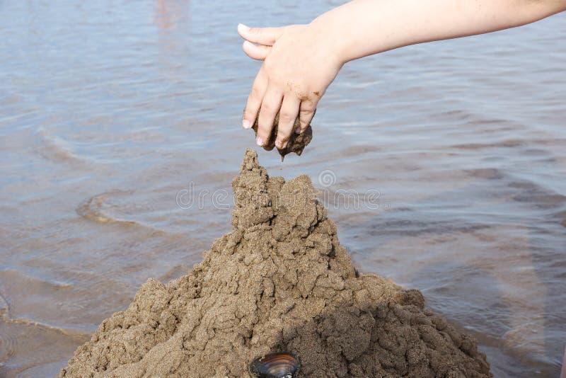 handen av barnet bygger en sandslott på stranden på bet royaltyfri fotografi