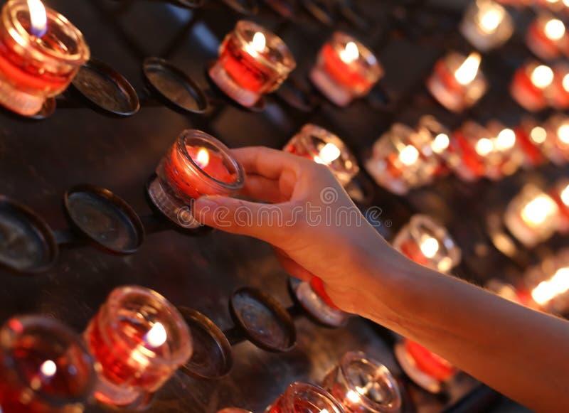 handen av barnet vänder på en stearinljus i kyrka, och därefter säger hon en pr royaltyfri foto