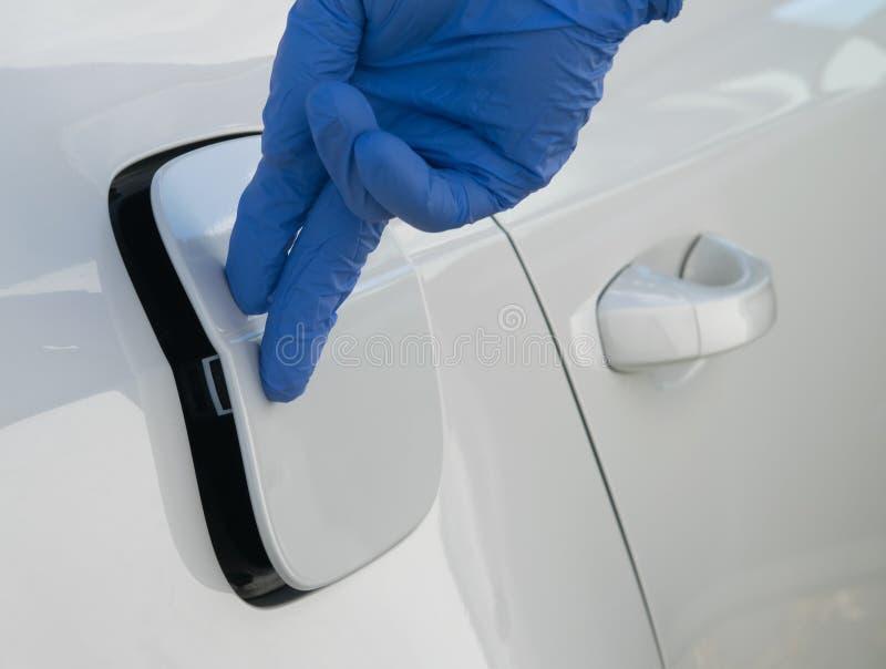 Handen av en arbetare i en blå handske stänger luckan av gasbehållaren av bilen royaltyfria foton