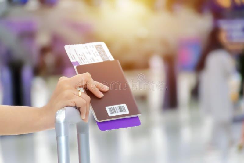 Handen av en kvinna som rymmer ett pass, en loppbiljett, är plac arkivbilder