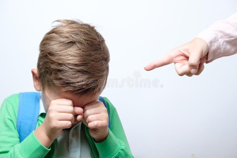Handen av en strikt lärare och den förskräckta skolpojken med blått vandrar royaltyfri fotografi