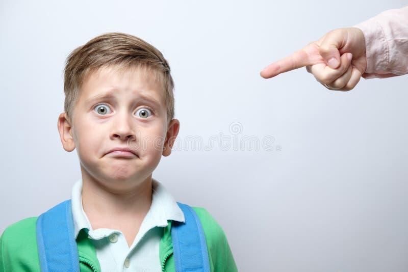 Handen av en strikt lärare och den förskräckta skolpojken med blått vandrar arkivfoto