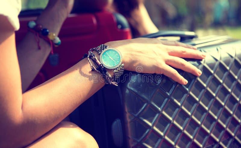 Handen av en ung flickahandelsresande på en resväska som väntar på drevet royaltyfri fotografi