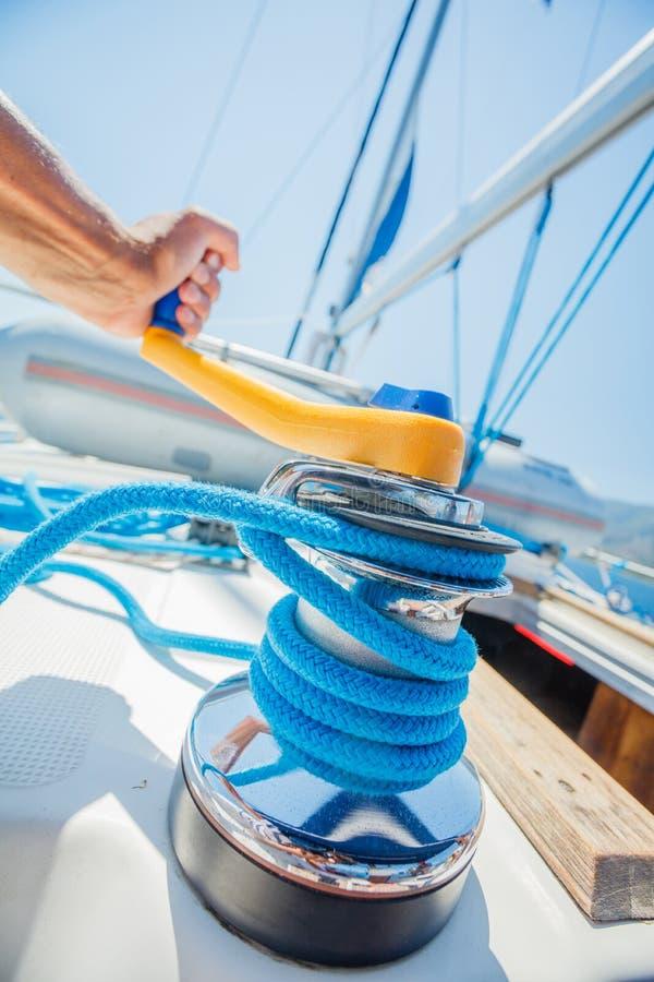 Handen av kaptenen seglar fartyget som arbetar på fartyget med vinschen på en segelbåt Yachtredskap under havresan som seglar arkivbild