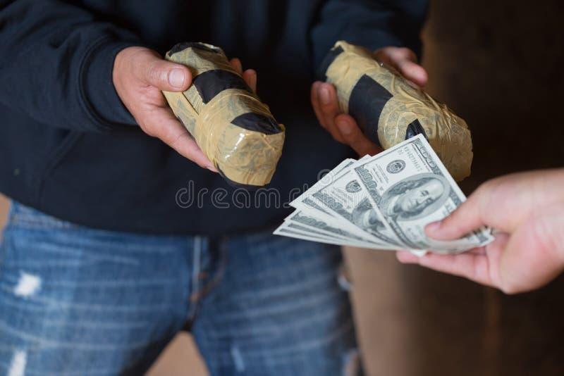 Handen av knarkaremannen med pengarköpandedosen av kokain eller hjältinnan, stänger sig upp av köpande dos för knarkare från knar royaltyfri fotografi