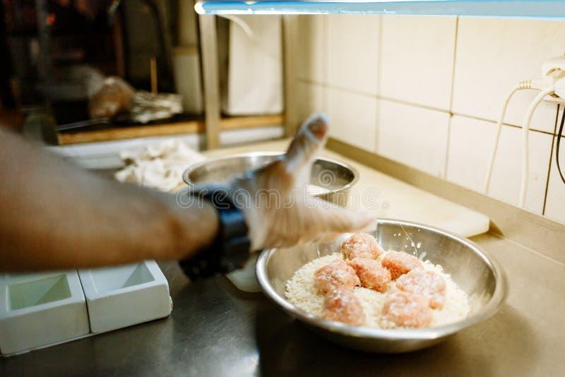 Handen av kocken lagar mat kotletter, i att panera royaltyfri bild