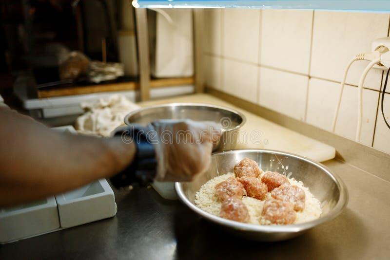 Handen av kocken lagar mat kotletter, i att panera arkivbild