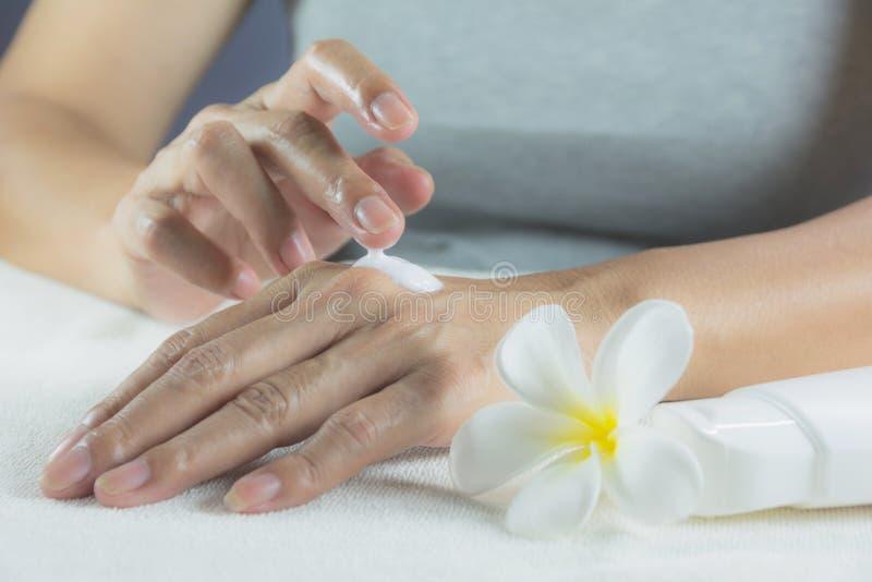 Handen av kvinnan applicerar lotion på hud av den tillbaka handen fotografering för bildbyråer