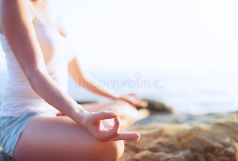 Handen av kvinnan som mediterar i en yoga, poserar på stranden royaltyfri bild