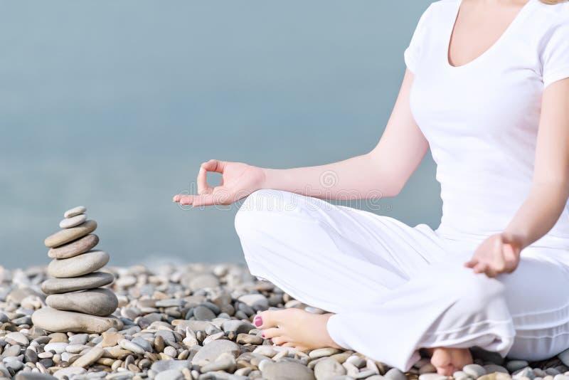 Handen av kvinnan som mediterar i en yoga, poserar på stranden royaltyfria foton