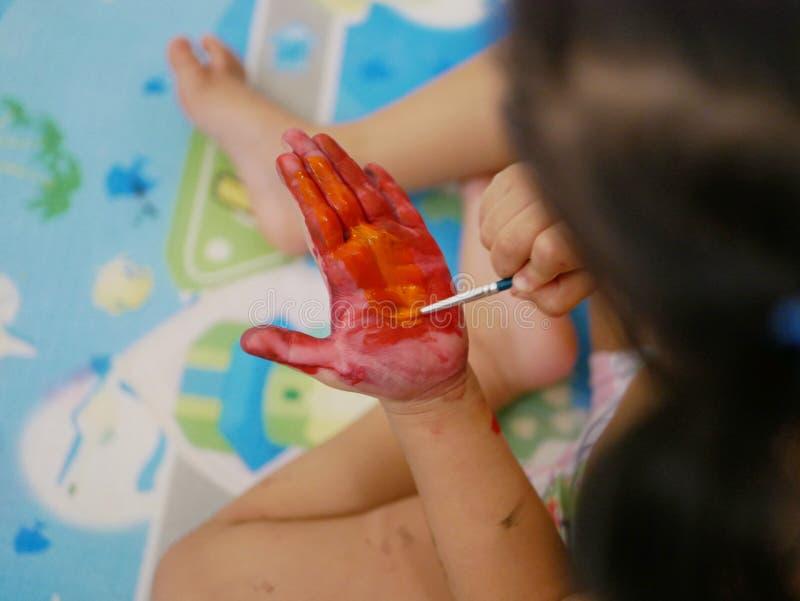 Handen av lite att behandla som ett barn att målas med röda och orange färger - behandla som ett barn handprint-/fingeravtryck arkivfoton