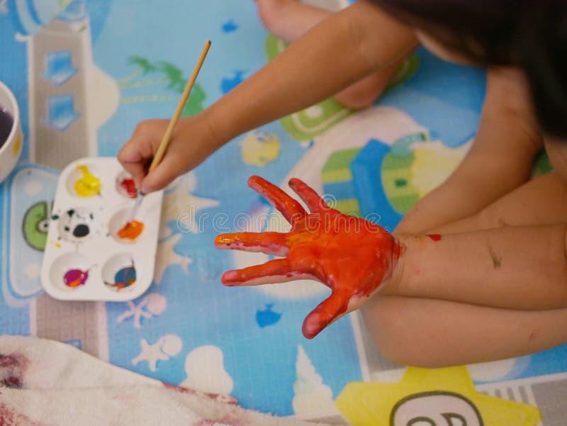 Handen av lite att behandla som ett barn att målas med röda och orange färger - behandla som ett barn handprint-/fingeravtryck royaltyfri foto