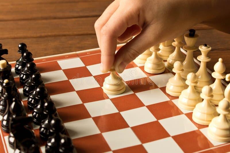 Handen av lite flickan som spelar schack close upp arkivbild