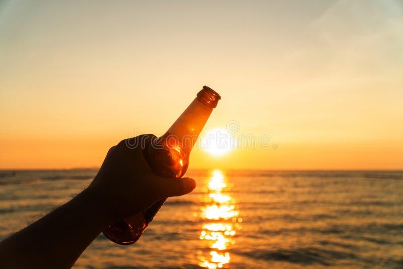 Handen av mannen rymmer ölflaskan och rymmer hans hand upp på himlen i afton med solnedgång fira på ferie på stranden in royaltyfria foton