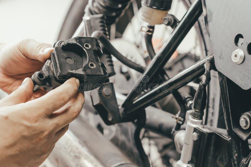 Handen av mekanikermannen byter ut och justerar den sy bakre bromsen för motorcykeln arkivfoto