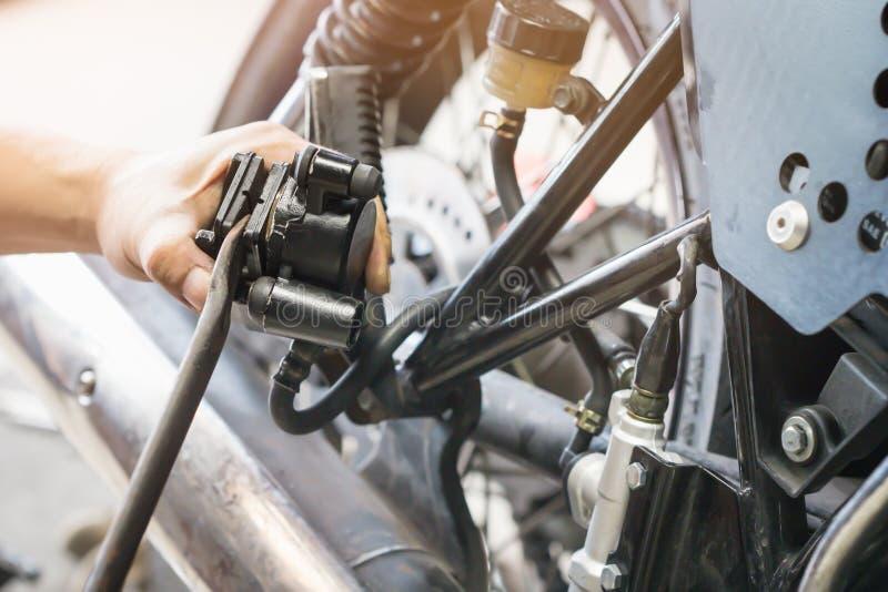 Handen av mekanikermannen byter ut och justerar den sy bakre bromsen för motorcykeln arkivbild