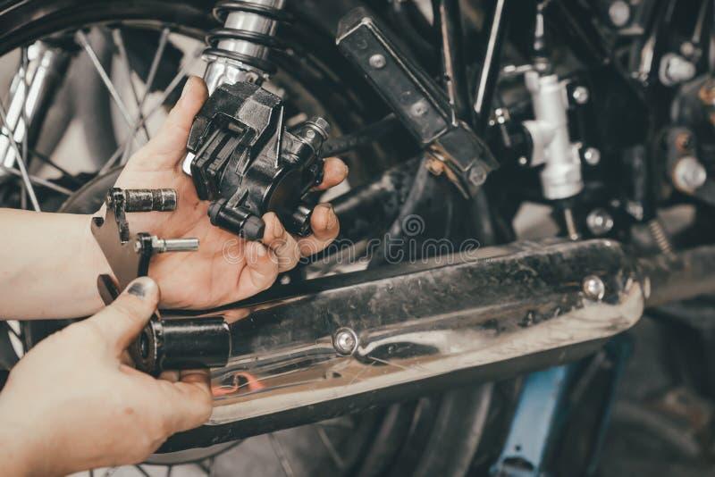 Handen av mekanikermannen byter ut och justerar den sy bakre bromsen för motorcykeln royaltyfria foton