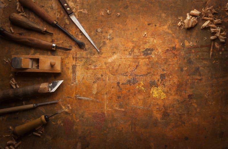 Handen bearbetar trä på en gammal träarbetsbänk arkivbild
