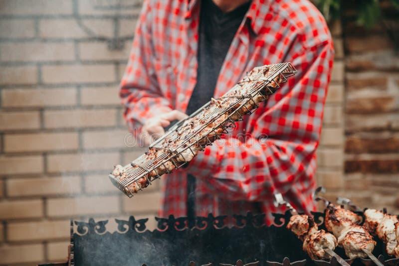 Handen bläddrar grillfestgallret på galler arkivfoto