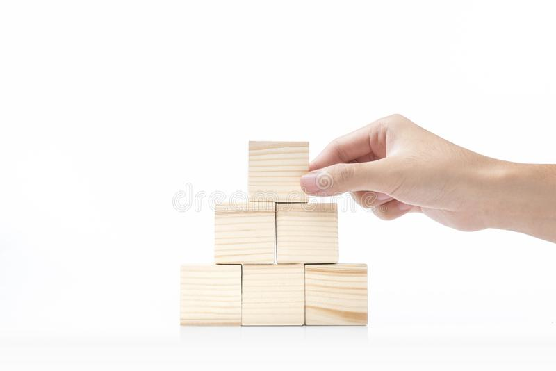 Handen bygger en pyramid från ett träkvarter royaltyfri bild