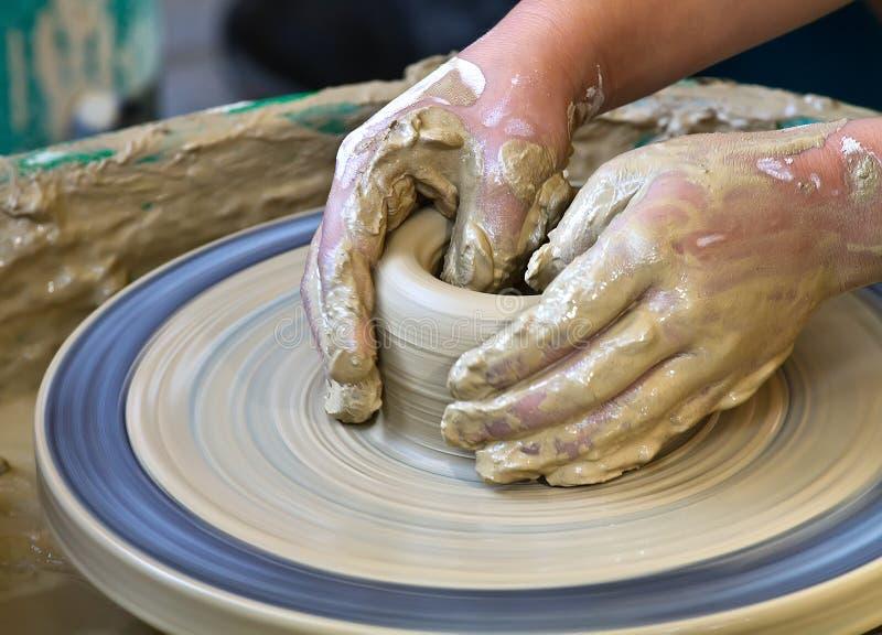 Handen die aan aardewerk werken stock foto
