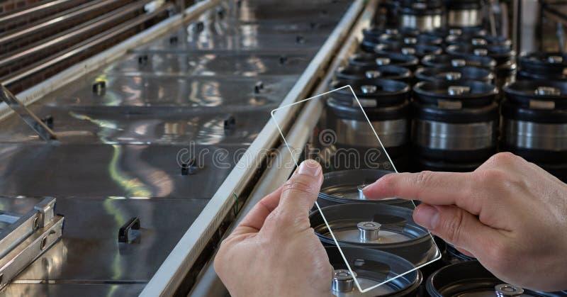 Handen die beeld van containers nemen door transparant apparaat bij brouwerij royalty-vrije stock foto
