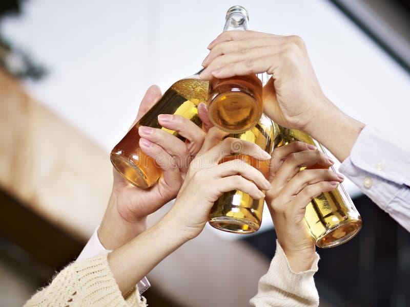 Handen die bierflessen voor een toost opheffen stock foto's