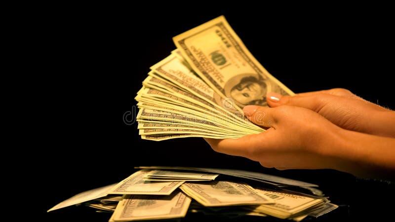 Handen die bundel van dollars houden, witwassen van geld, onwettige zaken, terugslag stock afbeelding