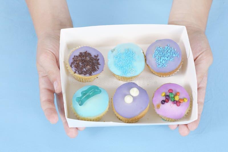 Handen die cakes houden royalty-vrije stock afbeelding