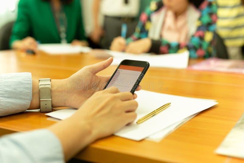 Handen die celtelefoon met de grafiek van het voorraadgeld met groep bedrijfsmensen met behulp van stock foto