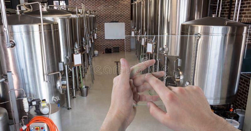 Handen die containers fotograferen door transparant apparaat bij brouwerij stock afbeeldingen