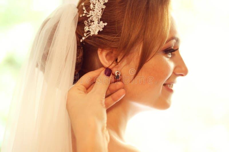 Handen die de bruid met oorringen helpen royalty-vrije stock afbeeldingen