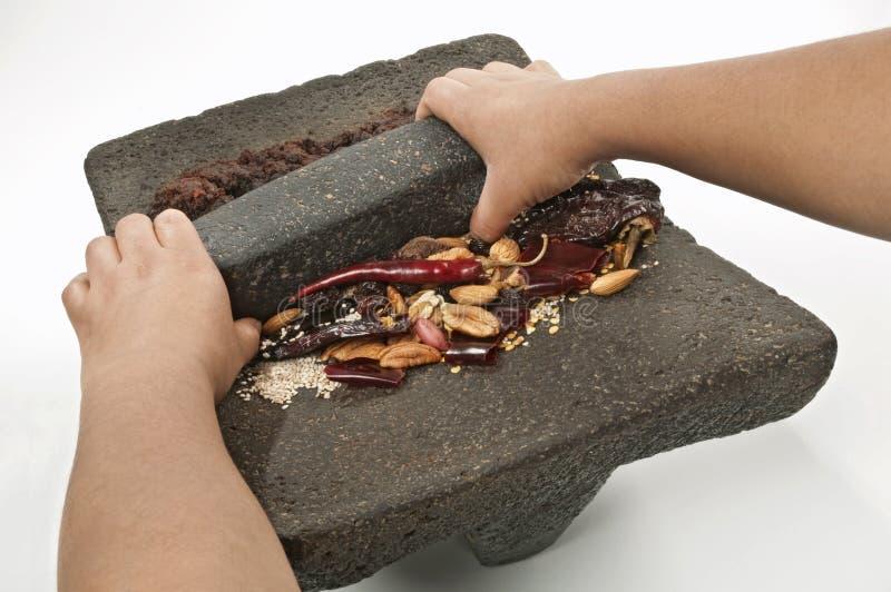 Handen die de ingrediënten malen om trad voor te bereiden stock afbeelding