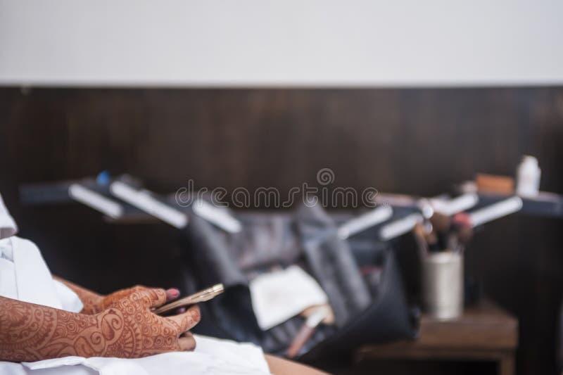 Handen die de telefoon van de hennaholding dragen stock afbeelding