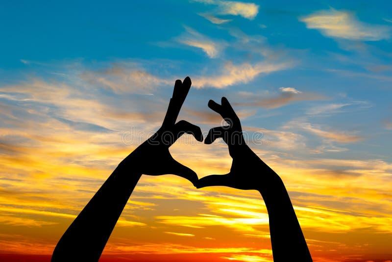 Handen die een hart vormen bij zonsondergang stock illustratie