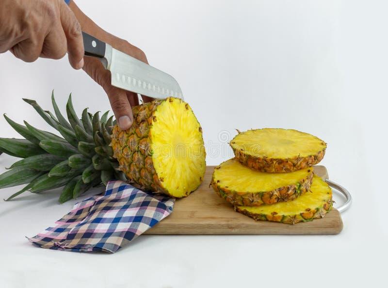Handen die een heerlijke ananas snijden royalty-vrije stock fotografie