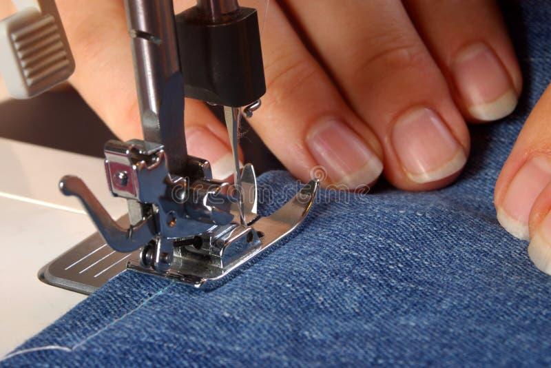 Handen die een naaimachine met behulp van royalty-vrije stock fotografie