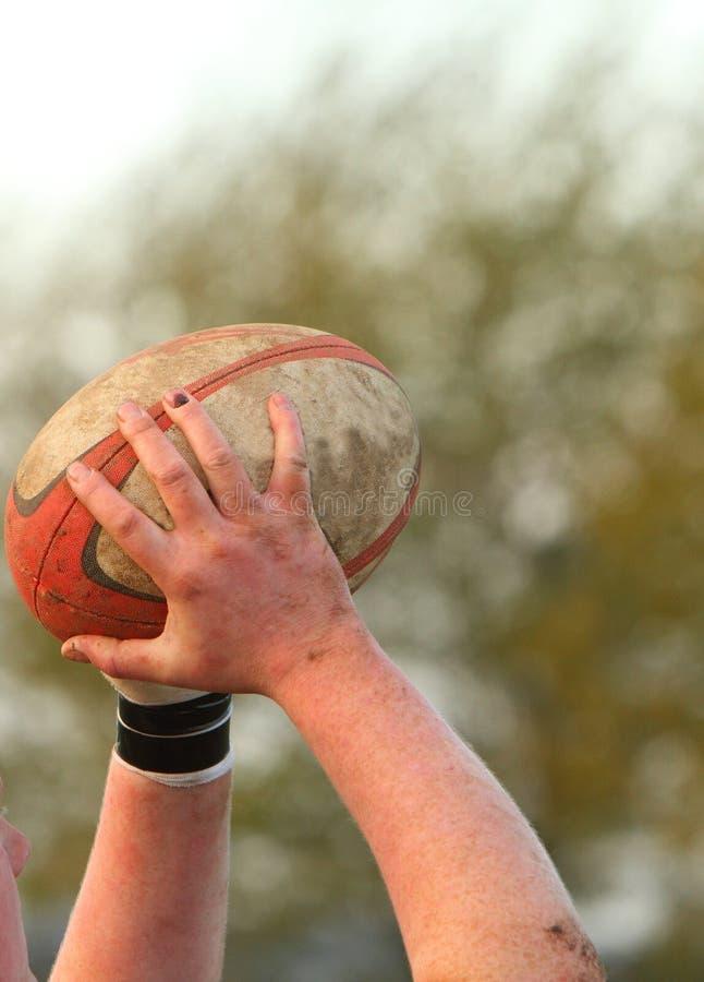 Handen die een rugbybal houden stock afbeelding