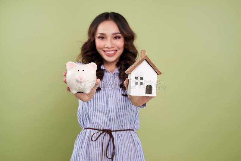 Handen die een spaarvarken en een huismodel houden De huisvestingsindustrie m royalty-vrije stock afbeelding