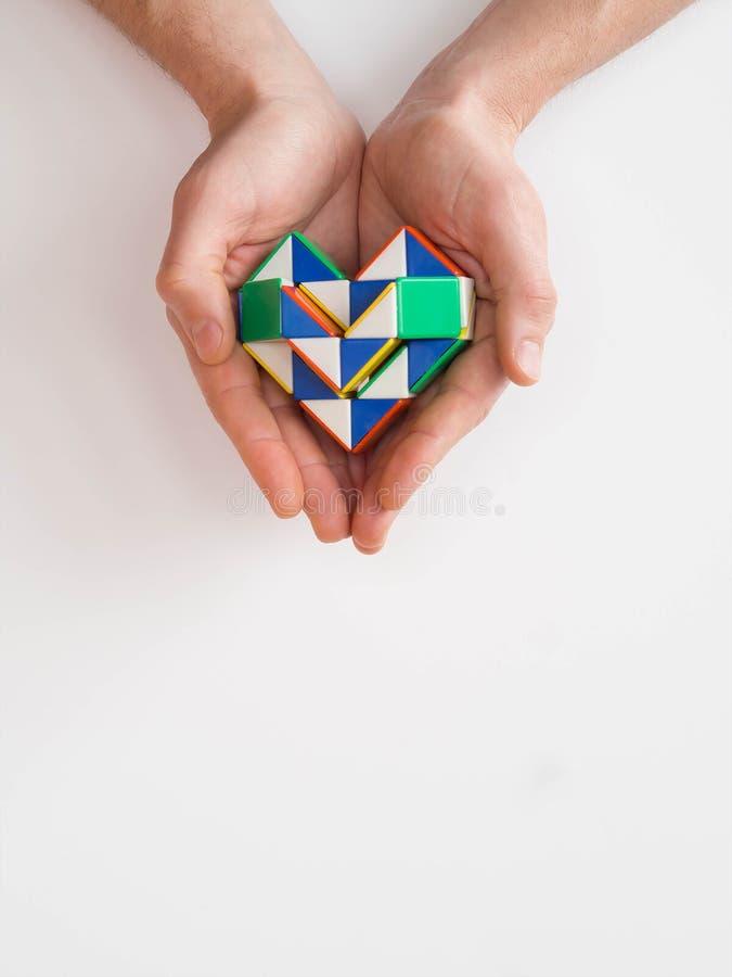 Handen die een stuk speelgoed van de hartdraai houden stock afbeeldingen
