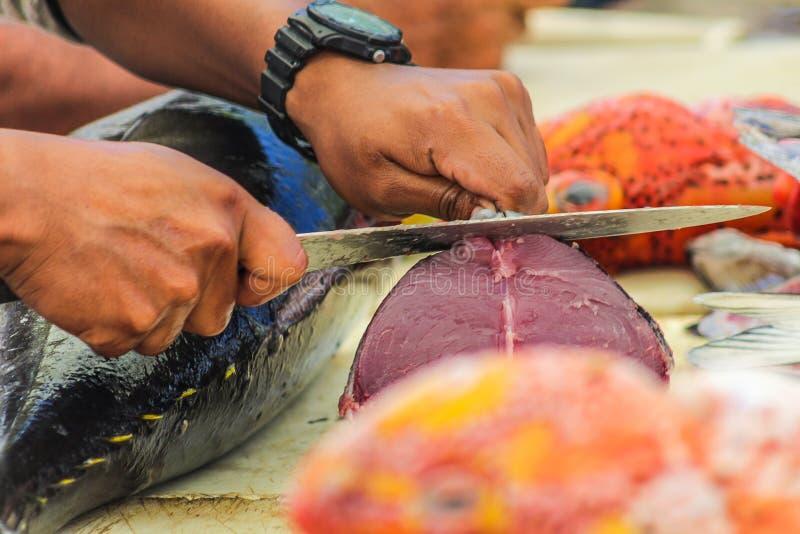 Handen die een stuk van tonijn snijden bij een marktkraam in een kleine haven royalty-vrije stock fotografie