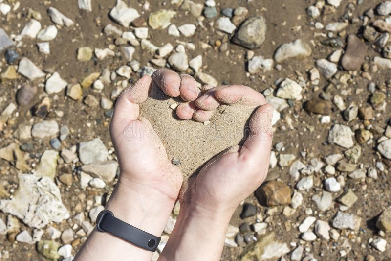 Handen die een zand in de palmen van hart, het concept houden die het leven uit als zand vingers doornemen stock fotografie