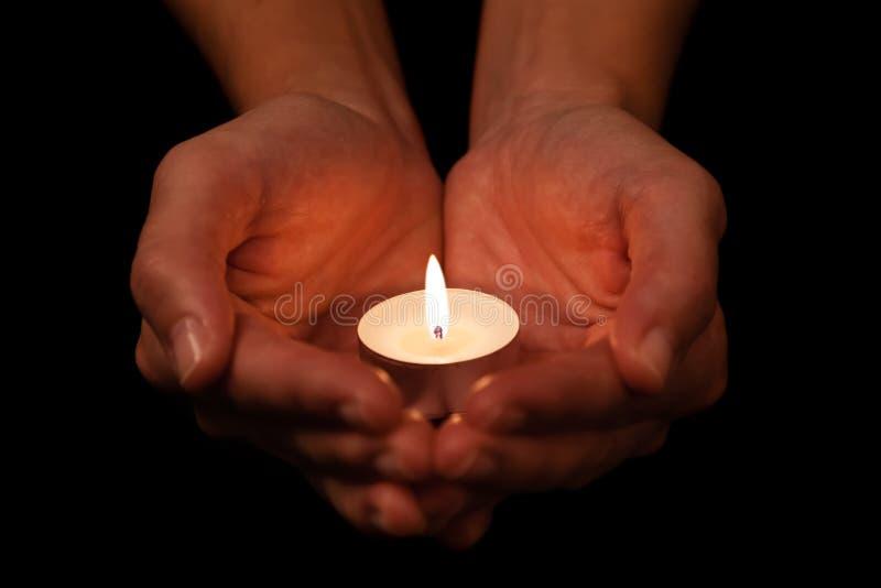 Handen die en aangestoken of het branden kaarskaarslicht op duisternis houden beschermen royalty-vrije stock afbeelding