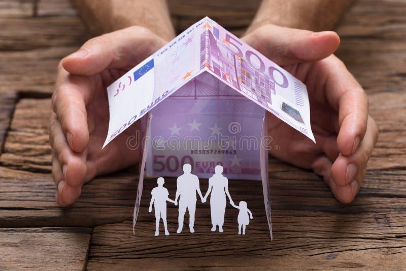 Handen die Familie omvatten die onder Huis van Euro Nota's wordt gemaakt royalty-vrije stock foto